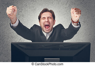 emotional young businesman rejoices win at the computer