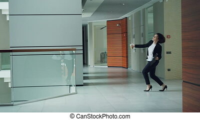 Emotional young lady businesswoman is dancing in hall of...