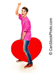 Emotional young man posing with big red heart. Isolated over white background.