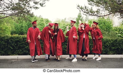 Emotional young people in mortar-boards and gowns are dancing and laughing having fun with green trees and nature in background. Education and celebration concept.