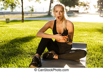 Emotional young sports woman outdoors sitting on grass using phone.