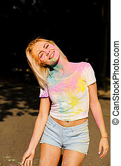 Emotional young woman in white t shirt and jeans shorts covered with colorful Holi powder