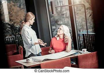 Emotional young woman telling a nice story to her colleague