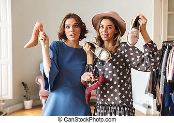 Emotional young women choosing shoes.