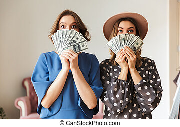 Emotional young women indoors holding money.