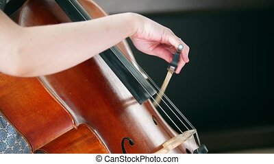Emotionally playing the cello in the room in daylight. Mid...