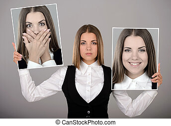A young business woman holds two portraits of different emotions to choose from today. Gray background