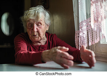 Emotions of elderly woman sitting at the table. 90 year old.