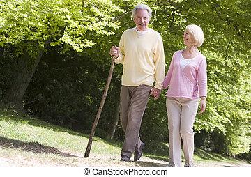 emparéjese andando, en, trayectoria, en el estacionamiento, manos de valor en cartera, y, sonriente