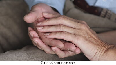 Empathic older family couple stroking hands of each other...