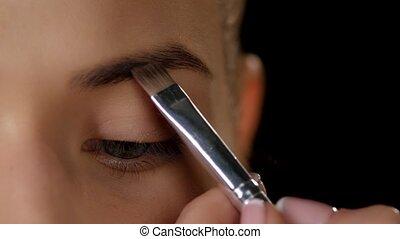 Emphasize eyebrows. Makeup. Closeup - Beautiful woman draw...