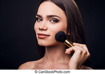 Emphasizing her cheekbones. Smiling young woman holding make-up brush near her cheek while standing against black background