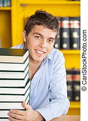 empilhado, biblioteca, livros, estudante, tabela, sorrindo