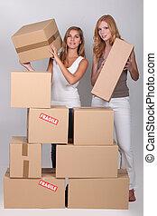 empilhando, caixas, mulheres jovens