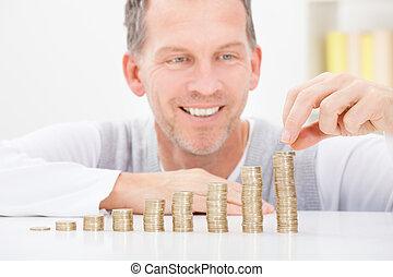 empilhando, moedas, homem maduro