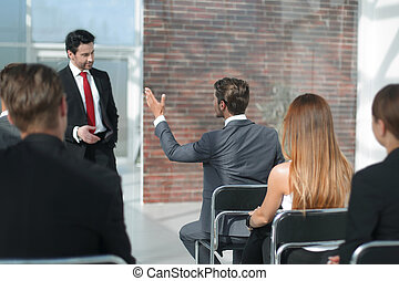 employee asks a question at a business meeting