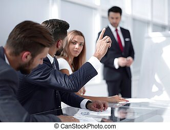 employee at the presentation raise their hands to ask a question