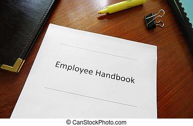 Employee handbook document on an office desk...