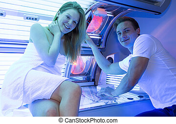 Staff employee in a solarium counseling customer or client at tanning bed