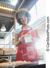 Employee in red apron holding box