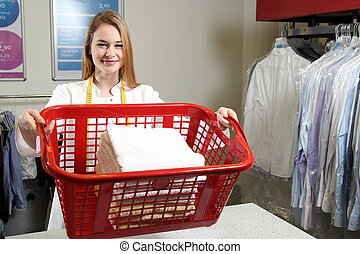 Employee of a dry cleaning with a  laundry basket