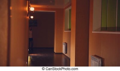 employee of hotel manager is a woman in the evening along the corridor yellow light