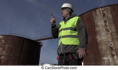 Employee on walkie talkie near tanks