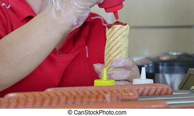 Employee prepares top loader hotdog in fast food takeaway restaurant