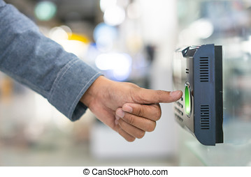 Employee scanning fingerprint record hours work time.