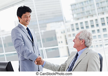 Employee shaking the hand of his manager