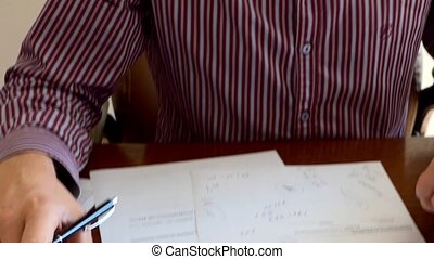 Employee Working With a Calculator And Writing Down Something in an Office