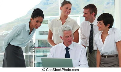 Employees around their boss looking a laptop screen