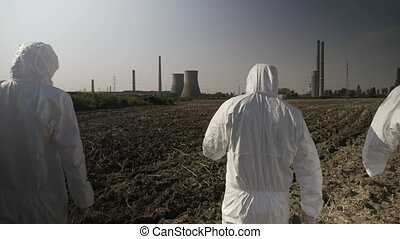 Employees ecologists team in hazmat suits looking at...