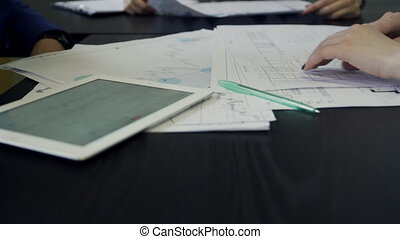 Employees examining documents lying in front of them on table indoors. Young colleagues sitting in office of company and carefully look at papers that show lot of color charts, diagrams and tables. They are knowledgeable and have extensive experience in economic and juristical sphere analyzing ...