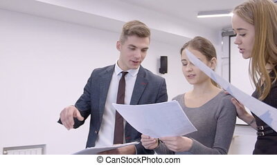 Employees of office study schedule of sales and pleased with...