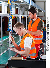 Employees working next to machine in a factory