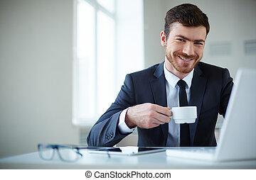 Employer at work - Handsome businessman having tea or coffee...