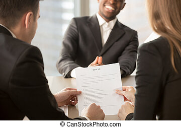 Employers recruiters reviewing resume, happy applicant at backgr