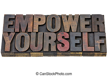 empower yourself - motivation concept - isolated text in vintage letterpress wood type blocks stained by ink