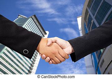 empresarios, sacudarir las manos, contra, cielo azul, y, edificio moderno
