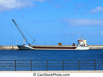 Emprty container ship in a harbour prior to loading with crane on the dock and blue sky and railings