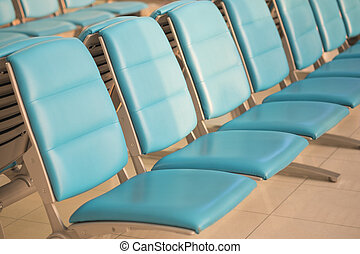 Empty airport terminal waiting area with blue chairs
