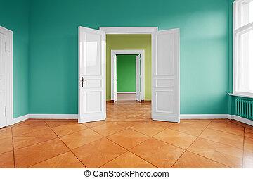 empty apartment room with wooden floor and open wing doors -
