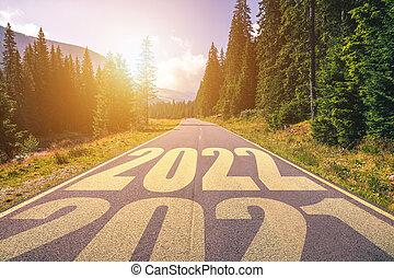 Empty asphalt road and New year 2022 concept. Driving on an empty road in the mountains to upcoming 2022 and leaving behind old 2021. Concept for success and passing time.