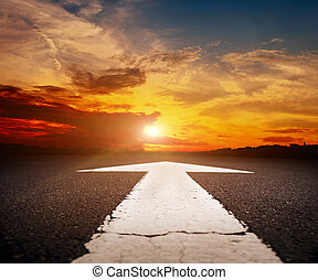 Empty asphalt road with the arrow at sunset