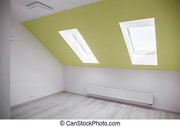 Empty attic room with white and green walls