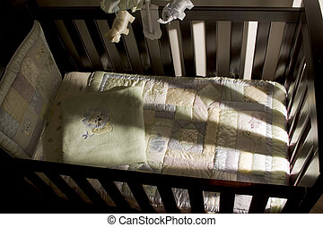 Empty baby cot with harsh side lighting coming through the slats