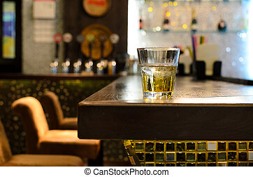 Empty bar with a tumbler of whiskey on the counter