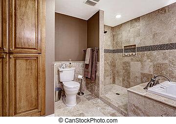 Empty bathroom interior. Light brown tile, bath tub and toilet