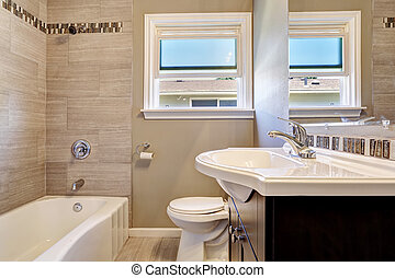 Modern bathroom interior with window and tile wall trim. Empty house interior